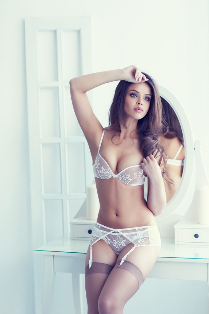 Beautiful alluring young woman in white sexy lingerie posing indoor