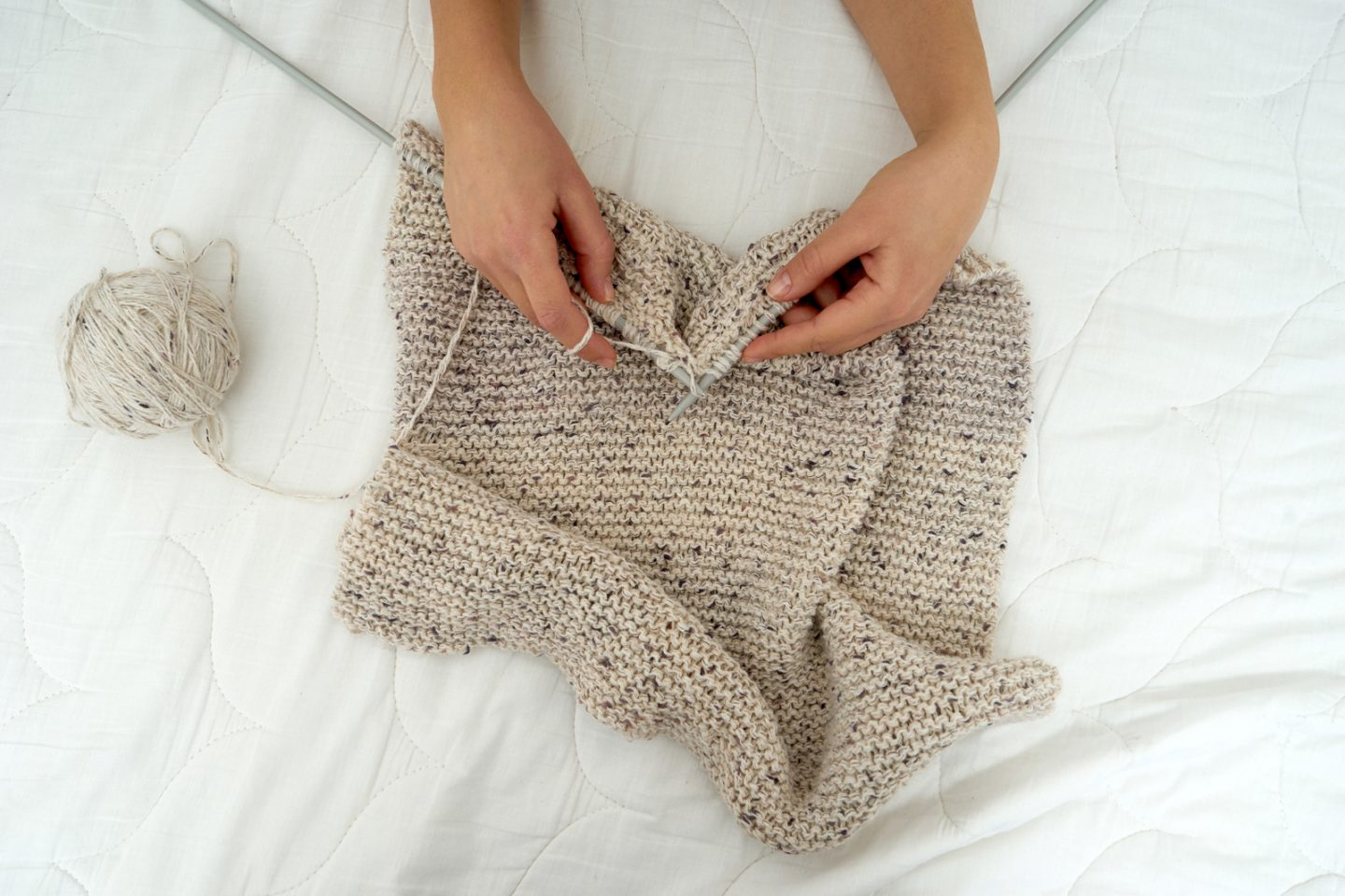 Close-up of young woman hands, knitting scarf