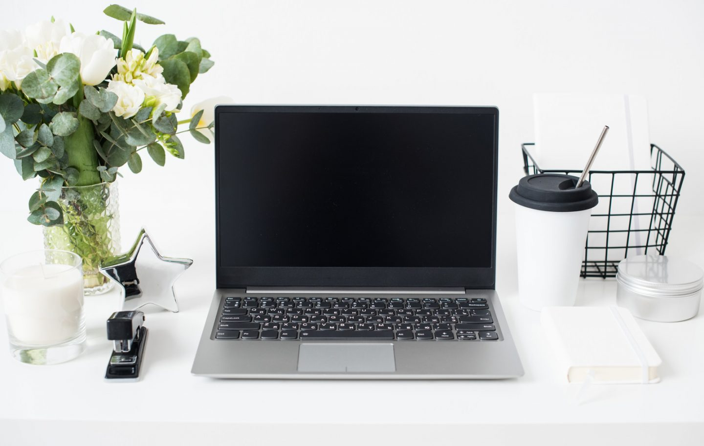Hipster bloggers work place, laptop and flowers on white tabletop, trendy office decoration