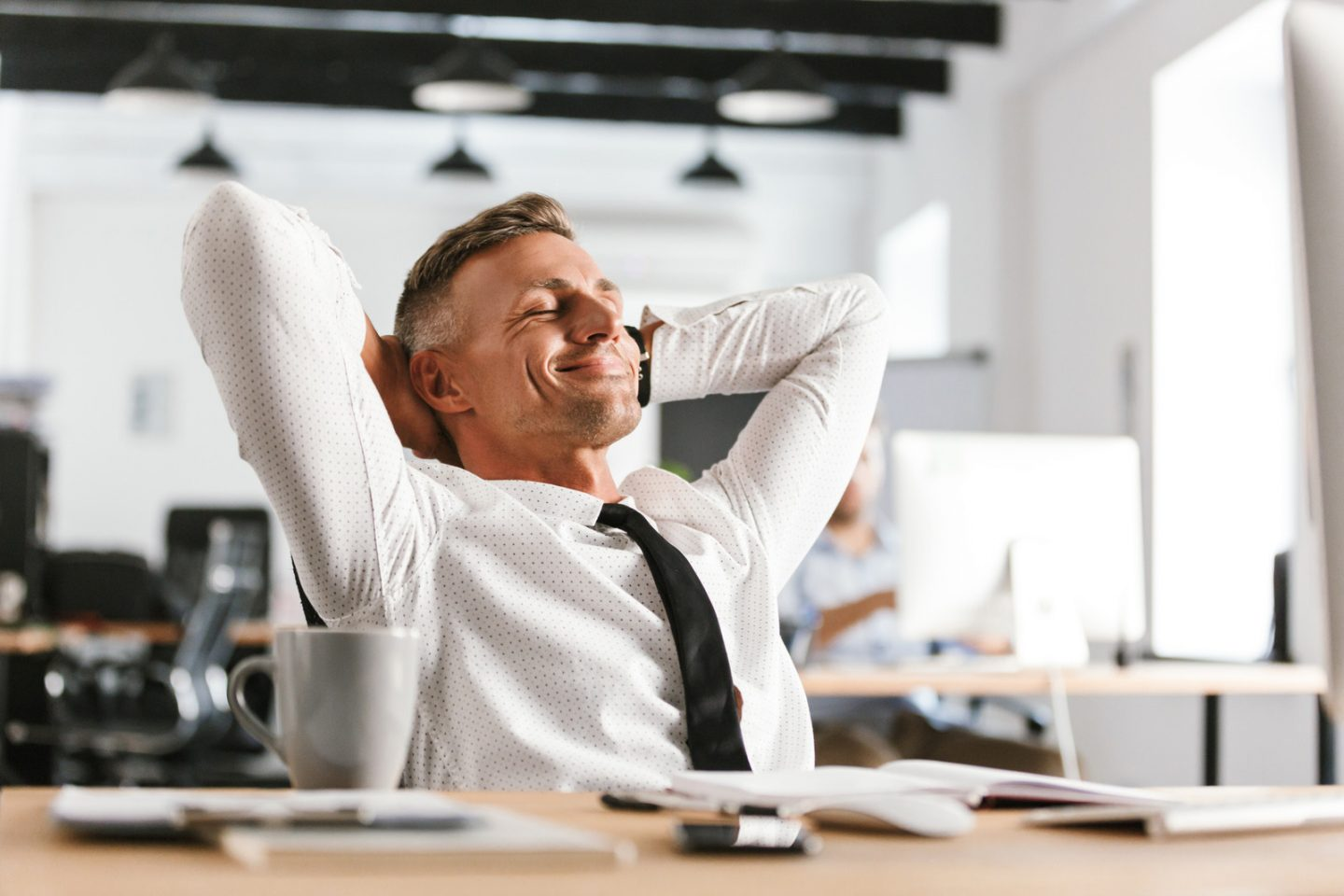 Image of Pleased middle aged business man relaxing while sitting by the table in office