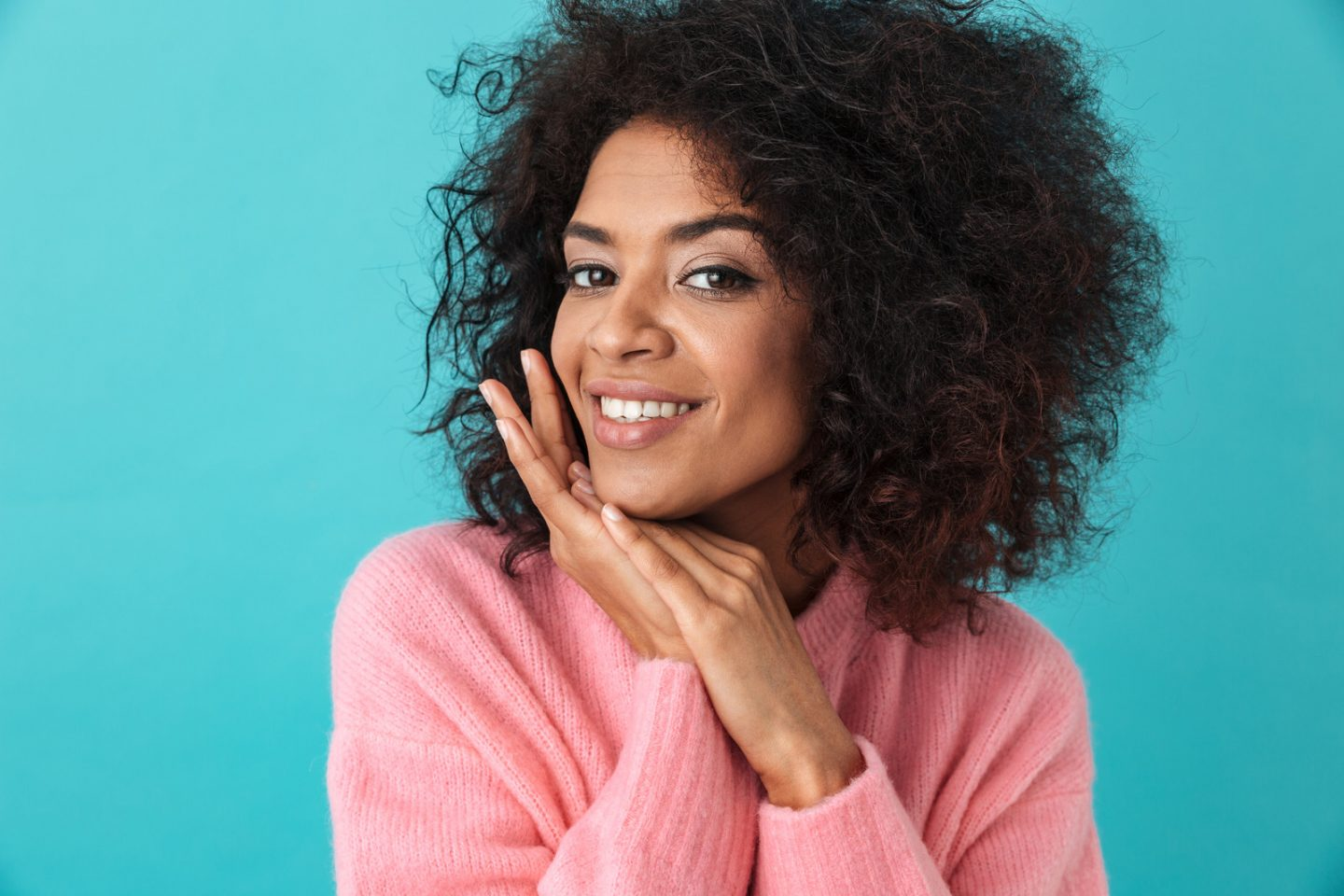 Multicolor image of pretty woman 20s with afro hairstyle smiling on camera with holding hands at face isolated over blue background