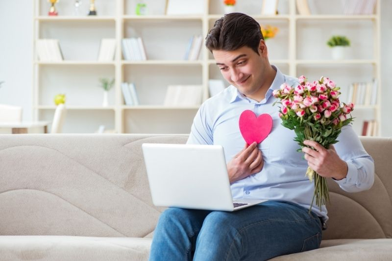 young man bringing flowers to his virtual date
