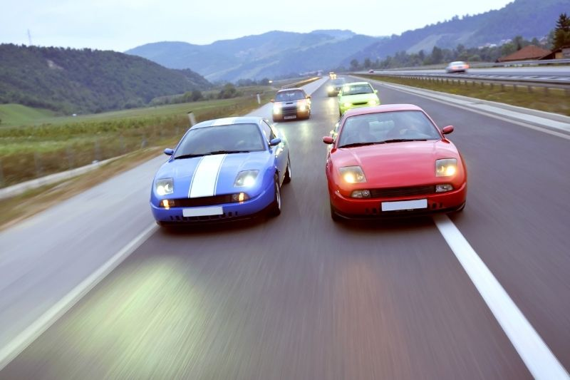 two hot tuning cars racing down the highway