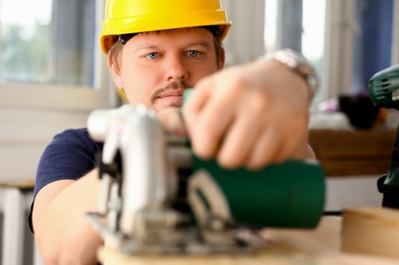 worker using an electric saw - manual job