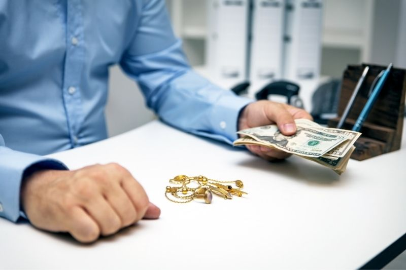 pawnbroker buying gold jewelry at a pawn shop